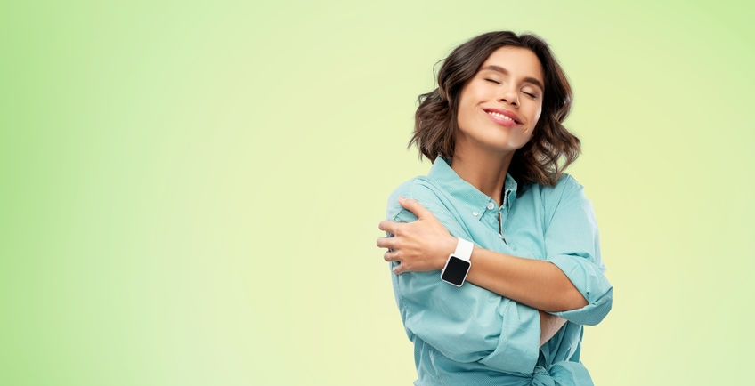 smiling woman with smart watch hugging herself